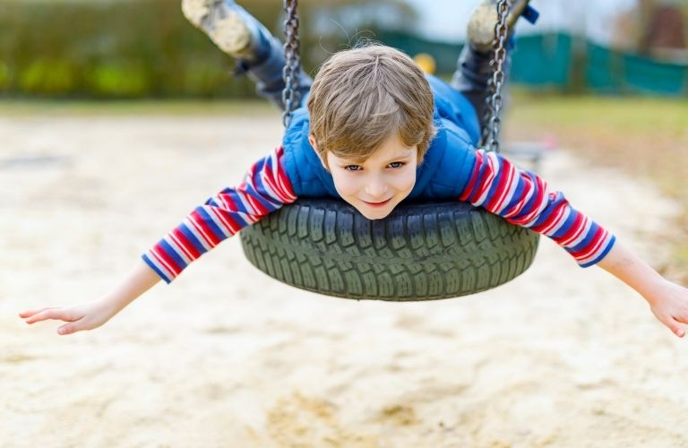 A child hanging onto a tire